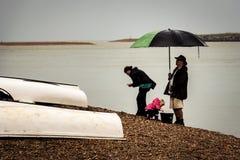 Familie am Strand an einem regnerischen Tag Lizenzfreies Stockfoto