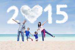 Familie am Strand unter Wolke von 2015 Stockbilder