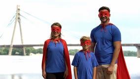 Familie in supermankostuums die voor camera, ouderlijk steun en zorgconcept stellen stock afbeeldingen