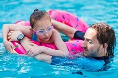 Familie am Swimmingpool stockbilder