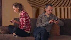 Familie, Technologie, Verhältnis-Schwierigkeiten und Leutekonzept - Paar mit den Smartphones, die zu Hause simsen stock video