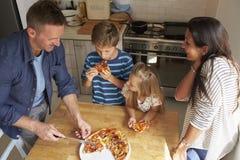 Familie thuis in Keuken die Eigengemaakte Pizza samen eten Stock Afbeelding
