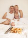 Familie thuis met popcorn stock afbeelding