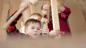 Familie, timmerwerk, houtbewerking en mensenconcept de vader onderwijst zoonstimmerwerk stock footage