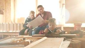 Familie, timmerwerk, houtbewerking en mensenconcept de vader onderwijst zoonstimmerwerk stock videobeelden