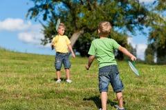Familie - twee kleine jongens die badminton spelen openlucht Royalty-vrije Stock Foto