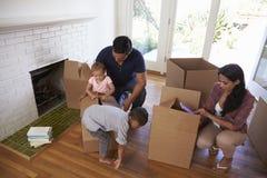 Familie Uitpakkende Dozen in Nieuw Huis bij het Bewegen van Dag royalty-vrije stock afbeeldingen
