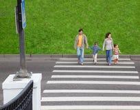 Familie und Überfahrtstraße Stockfotografie