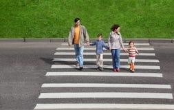 Familie und Überfahrtstraße, grüner Zaun und Gras Lizenzfreie Stockfotografie