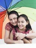 Familie und ein Regenbogenregenschirm Lizenzfreies Stockbild
