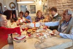 Familie und Freunde genießen auf Weihnachtsessen- und Austauschgeschenken zusammen stockfotografie