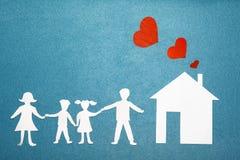 Familie und Hauptliebeskonzept Papierhaus und Familie auf blauem strukturiertem Hintergrund Rote Herzen vom Rohr zu Hause Glückli Stockbilder