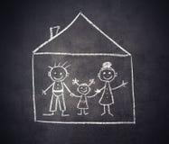 Familie und Haus werden mit Kreide auf einer Tafel gezeichnet Lizenzfreie Stockfotos