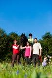 Familie und Kinder, die mit Pferd aufwerfen Lizenzfreie Stockbilder