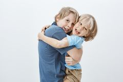 Familie und positives Gefühlkonzept Erfüllter glücklicher blonder Junge, der Bruder umarmt und Kamera mit erfreutem anstarrt Stockbild