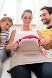 Familie und schwangere Mama, die Kopfhörer auf Babybauch verwendet Stockfotos