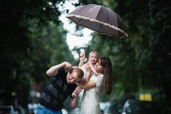 Familie unter dem Regen Lizenzfreie Stockbilder