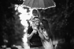 Familie unter dem Regen Stockbild