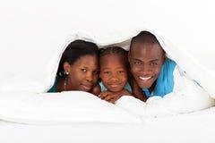 Familie unter Duvet lizenzfreie stockfotografie