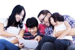 Familie unter Verwendung der Berührungsfläche auf dem roten Sofa - lokalisiert Lizenzfreies Stockbild