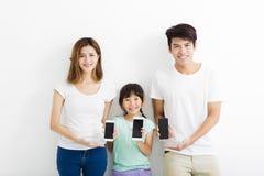 Familie unter Verwendung der intelligenten Telefone bei zusammen stehen Lizenzfreies Stockfoto