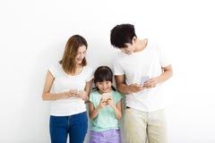 Familie unter Verwendung der intelligenten Telefone bei zusammen stehen Lizenzfreie Stockfotografie