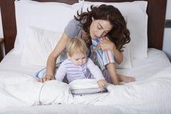 Familie unter Verwendung der Tablette auf Bett Lizenzfreies Stockfoto