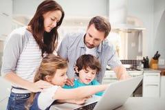 Familie unter Verwendung des Laptops auf Tabelle Stockbild