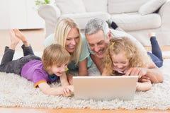 Familie unter Verwendung des Laptops zusammen beim Lügen auf Wolldecke Stockfotos