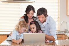 Familie unter Verwendung eines Notizbuches zusammen Stockfotografie