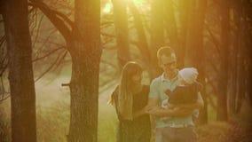 Familie van drie de naderbij komende camera die samen in het park gaan De vader die zijn zoon in hand houden De gelukkige familie stock video