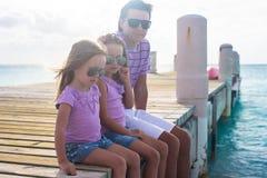 Familie van drie die bij het houten dok genieten zitten van stock afbeelding