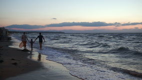 Familie van drie die blootvoets langs de kust lopen stock video
