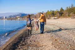 Familie van drie die door de Zwarte Zee in de winter lopen stock afbeeldingen