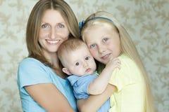 Familie van drie die en mensen binnenportret glimlachen koesteren Stock Foto's