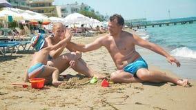 Familie van drie die hallo -hallo-fives op het strand geven stock video