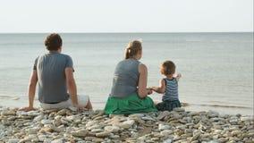 Familie van drie die op kiezelsteenstrand door zitten stock videobeelden