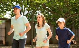 Familie van drie die openlucht lopen doen stock afbeeldingen