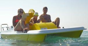 Familie van drie die water van rit op pedaalboot genieten stock videobeelden