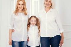 Familie van drie generaties die van vrouw wordt geschoten die samen stellen royalty-vrije stock fotografie