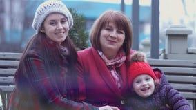 Familie van drie generaties van glimlachende vrouwen die op een bank in het stadspark zitten en handen houden Het concept van de  stock video