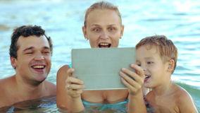 Familie van drie in overzees die op iets op stootkussen letten stock videobeelden