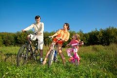 Familie van drie personen op fietsen in land. Royalty-vrije Stock Foto's