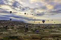 Familie van feeschoorstenen in Cappadoccia onder bewolkte hemel met hete luchtballons in de afstand royalty-vrije stock foto