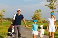 Familie van golfspelers het lopen Stock Foto's