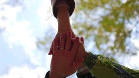 Familie van jonge plaats hun handen samen in het centrum van een cirkel stock videobeelden