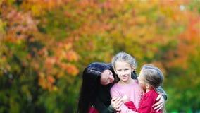 Familie van mamma en jonge geitjes in daling De jonge moeder en de meisjes genieten van de warme herfst stock videobeelden