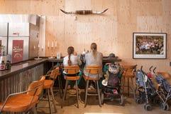 Familie van moderne Vikingen met kinderwagens die lunch hebben bij fast-food restaurant Stock Foto