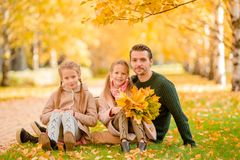 Familie van papa en jonge geitjes op mooie de herfstdag in het park stock afbeeldingen