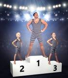 Familie van strongmans op winnaarsvoetstuk De vader en twee zonen in uitstekende kostuums De familie kijkt stock fotografie